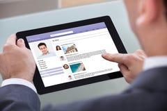 Close-up van de mens die op digitale tablet doorbladeren Royalty-vrije Stock Afbeelding