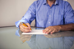 Close-up van de mens die op een stuk van document schrijven Royalty-vrije Stock Afbeeldingen