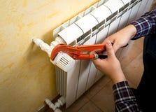 Close-up van de mens die radiatorklep met rode loodgieterbuigtang installeren Royalty-vrije Stock Fotografie