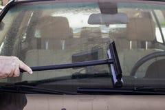 Close-up van de mens die rubberschuiver met behulp van om het windscherm van een auto met een zichtbare binnenkant van GPS op str royalty-vrije stock fotografie