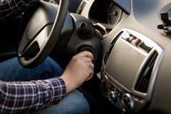 Close-up van de mens die sleutel opnemen in het slot van de autoontsteking stock afbeelding