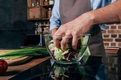 close-up van de mens wordt geschoten die salade mengen met handen die stock afbeelding