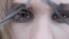 Close-up van de ogen van een jonge vrouw door prikkeldraad actie Het concept van de schoonheidsmanier stock videobeelden