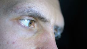 Close-up van de ogen en het gezicht van een jonge mens die bij een computer aan een Zwarte Achtergrond werken stock footage