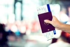 Close-up van de paspoorten van de vrouwenholding en instapkaart bij luchthaven stock afbeelding