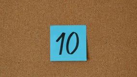 Close-up van de persoon die aantallen 0 tot 10 op de raad plakken Top 10 in tegenovergestelde richting stock videobeelden