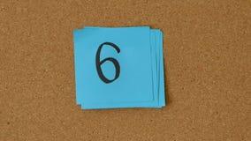 Close-up van de persoon die aantallen 10 tot 0 op de raad plakken Top 10 in tegenovergestelde richting stock footage