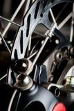 Close-up van de de remschijf van de staal het glanzende fiets op dark Stock Afbeeldingen