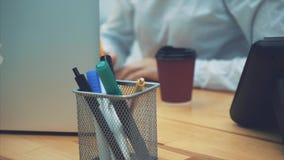Close-up van de tellers van pennenpotloden op de lijst Tijdens dit onscherpe jonge bedrijfsvrouwenwerk voor laptop Na een tijdje stock videobeelden