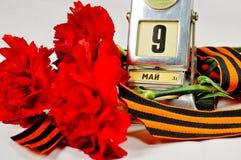 Close-up van de uitstekende kalender van het metaalbureau met 9 de datum en George van Mei lint en rode anjers Stock Foto's