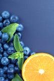 Close-up van de verse helft oranje, gezonde bosbessen en groene bladeren van munt op een donkerblauwe achtergrond De ruimte van h Royalty-vrije Stock Foto's
