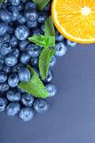 Close-up van de verse helft oranje, gezonde bosbessen en groene bladeren van munt op een donkerblauwe achtergrond De ruimte van h Stock Foto's