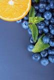 Close-up van de verse helft oranje, gezonde bosbessen en groene bladeren van munt op een donkerblauwe achtergrond De ruimte van h Stock Foto