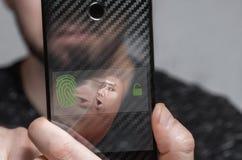 Close-up van de vingerafdruk om de gebruiker van de telefoon te identificeren het concept gezichtsidentiteitskaart stock foto's