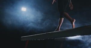 Close-up van de voet van een professioneel turnermeisje die in langzame motie in de rook op een evenwichtsbalk springen Vrouwen ` stock video