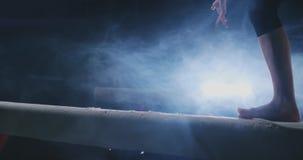 Close-up van de voet van een professioneel turnermeisje die in langzame motie in de rook op een evenwichtsbalk springen Vrouwen ` stock videobeelden