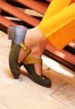 Close-up van de voeten van het wijfje in klassieke schoenen en gele elegante kleding royalty-vrije stock afbeelding