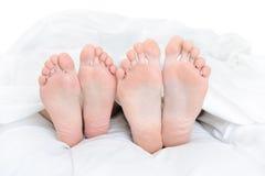 Close-up van de voeten van een paar op het bed Royalty-vrije Stock Foto's