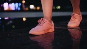 Close-up van de voeten van vrouwen in roze tennisschoenen In Motie Het meisje gaat door de stad bij nacht stock footage