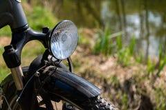 Close-up van de voorzijde van de fiets met een koplamp met een vage achtergrond van gras en vijver royalty-vrije stock foto's