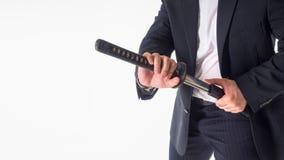 Close-up van de Witte Achtergrond van Zakenmanremoving sword over Royalty-vrije Stock Afbeelding