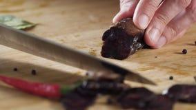 Close-up van de worst van messenbesnoeiingen scène Close-up van knipsel donkere salami op houten scherpe raad Zout op achtergrond stock footage