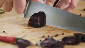 Close-up van de worst van messenbesnoeiingen scène Close-up van knipsel donkere salami op houten scherpe raad Zout op achtergrond royalty-vrije stock foto