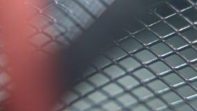 Close-up van de zilveren grijze omheining van het de draadnetwerk van het kleurenmetaal met lichtgrijze schaduw als achtergrond stock videobeelden