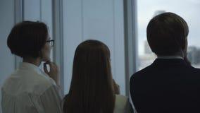 Close-up van drie bedrijfsmensen die dichtbij het venster in bureau en wat betreft hun eigen kinnen blijven Achter mening stock videobeelden