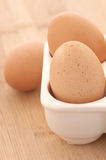 Close-up van Drie Bruine Eieren in een Karton op Hout Stock Foto's