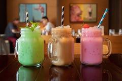 Close-up van drie verschillende op smaak gebrachte smakelijke Thaise melkthee op een houten lijst bij een koffie stock foto
