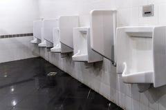 Close-up van drie witte urinoirs in de badkamers van mensen, ontwerp van witte ceramische urinoirs Stock Foto's