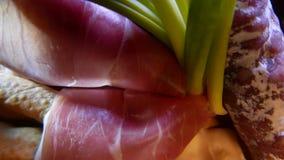Close-up van dunne plakken van varkensvleesham op de schotel met kaas en greens 4k UHD stock footage