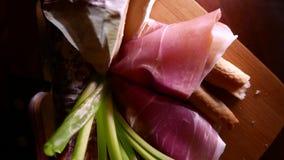 Close-up van dunne plakken van varkensvleesham op de schotel met kaas en greens 4k UHD stock videobeelden