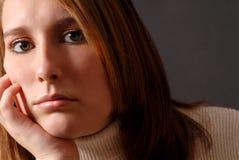 Close-up van een aantrekkelijke jonge vrouw met haar kin die op hij rust Stock Foto