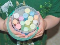 Close-up van een baby en een emmer van kleurpotloden stock foto