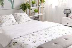 Close-up van een bed gekleed in het organische van het katoenen witte linnen groene installatiespatroon in een zonnig slaapkamerb royalty-vrije stock foto's