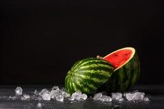 Close-up van een besnoeiing om rijpe watermeloen op een zwarte achtergrond Verfrissend zoete bes met kleine zwarte zaden op stock fotografie