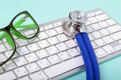 Close-up van een blauwe stethoscoop die op notitieboekjetoetsenbord en groene glazen liggen Selectieve nadruk Stock Foto's