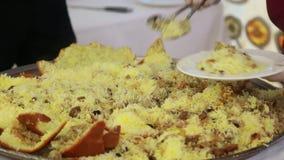 Close-up van een chef-kok` s chef-kok die een messen vaste die schotel snijden - pilau in brood wordt gebakken stock video