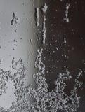 Close-up van een daling op het glas na regen en sneeuw die neer op een zachte achtergrond stromen stock foto