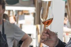Close-up van een de wijnglas van de mensenholding bij open voedselmarkt Royalty-vrije Stock Foto