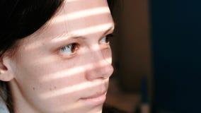 Close-up van een donkerbruin vrouwen` s gezicht met strepen van licht van het venster op haar gezicht stock videobeelden