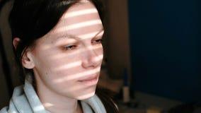 Close-up van een donkerbruin vrouwen` s gezicht met strepen van licht van het venster op haar gezicht stock video