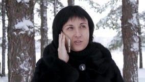 Close-up van een donkerbruine vrouw die zich tegen een bos of een park op een de winterdag bevinden Het meisje houdt haar smartph stock videobeelden