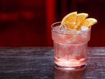Close-up van een Fitzgerald-cocktail in kort glas, jenever, die zich op die de barteller bevinden, op een rood lichtachtergrond w royalty-vrije stock fotografie