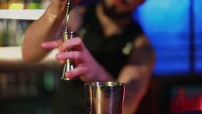 Close-up van een gebaarde barman die een cocktail voorbereiden bij de nachtclub stock video