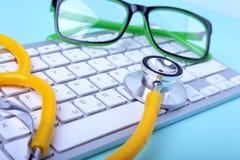 Close-up van een gele stethoscoop die op notitieboekjetoetsenbord en groene glazen liggen Selectieve nadruk Stock Foto's
