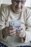 Close-up van een gelukkige hogere vrouw die Turkse Lirebankbiljetten tellen Stock Foto's