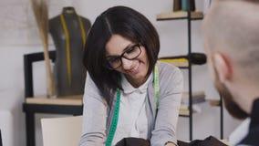 Close-up van een Glimlachende Kaukasische kleermaker die diverse stof aanbieden aan haar cliënt in atelier Zakenman bezoekende na stock video